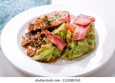 grilled cabbage with pork chop topped with bacon, mushrooms and onions, a ketogenic diet meal