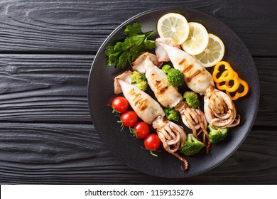 grilled calamari with tentacles with tomatoes, broccoli, lemon and pepper closeup on a plate on a table. Horizontal top view from above