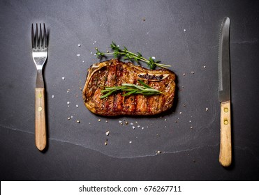 Grilled calf's cutlet with cutlery, top view