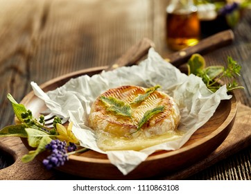 Grilled camembert cheese with addition of herbs on a wooden plate, Grilled vegetarian food, bbq