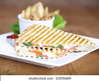 Grilled caprese sandwich with fried potatoes and ketchup on a plate