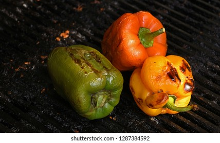 grilled capsicum. red yellow green capsicum grilled on a charcoal grill.