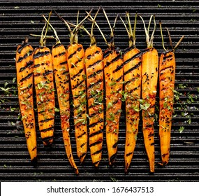 Grilled  carrots with the addition of olive oil herbs and seasoning  on the grill  top view