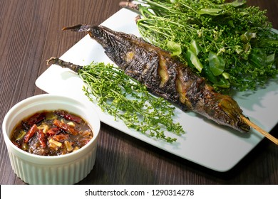 Grilled catfish and neem leaf which has blossom and sweet sauce, Thai season food / Select focus and dim light