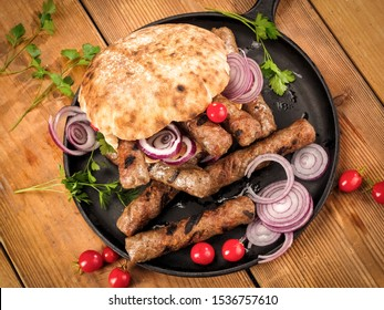Grilled cevapi with bread, onion, cherry tomatoes and parsley on wooden table, top view