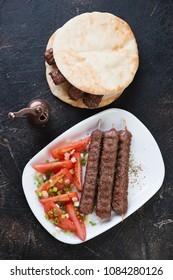 Grilled cevapi or cevapcici sausages with tomatoes and pita bread, view from above on a dark brown stone background