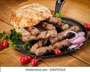 Grilled cevapi with roasted bread bun in a pan on wood