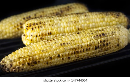 Grilled, charred corn on the cob with a dark background close up