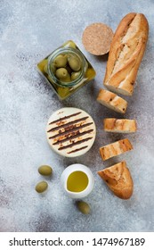 Grilled cheese, baguette, olive oil and olives over beige stone background, flatlay, vertical shot