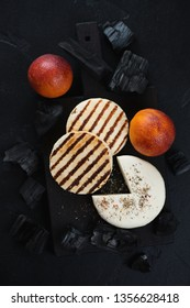 Grilled cheese and blood oranges, flatlay on a black stone background with charcoals, vertical shot