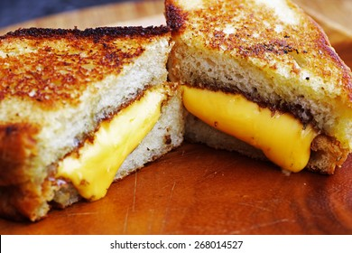Grilled cheese sandwich made with cheddar and thick rosemary bread on wood serving platter