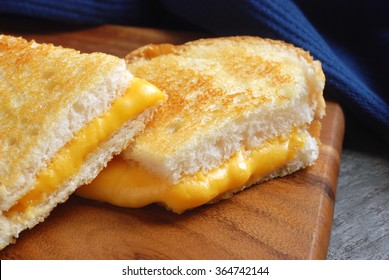 Grilled cheese sandwich  (made with thickly sliced french bread) on wooden cutting board.  Closeup with selective focus on front edge of sandwich.