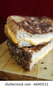 Grilled cheese sandwich with melted cheese on wood plate