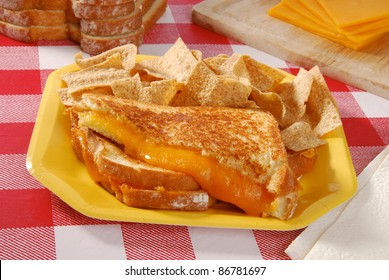 A grilled cheese sandwich on a checkered table cloth