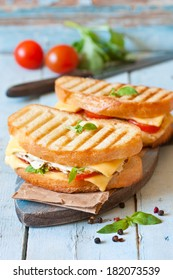 Grilled cheese sandwiches with chicken and tomatoes on a rustic wooden board.