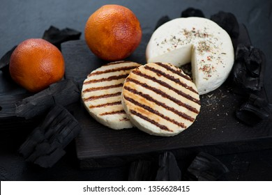 Grilled cheese and sicilian oranges on a black wooden chopping board with charcoals, studio shot