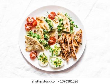 Grilled chicken, avocado cream cheese quesadilla, boiled eggs, vegetables - delicious snack, appetizer, tapas on a light background, top view