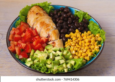 Grilled chicken with avocado, tomatoes, sweet corn, beans and lettuce. Southwestern colorful chicken salad with creamy cilantro dressing. horizontal
