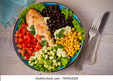 Grilled chicken with avocado, tomatoes, sweet corn, beans and lettuce. Southwestern colorful chicken salad with creamy cilantro dressing. View from above, top, horizontal