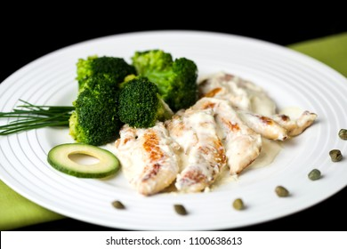 Grilled chicken with bechamel sauce, broccoli and avocado garnished with capers in a white round plate on a green cloth