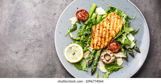 Grilled chicken breast asparagus arugula mushrooms tomatoes lemon and parmesan cheese. Seasonal salad from vegetables and poultry.