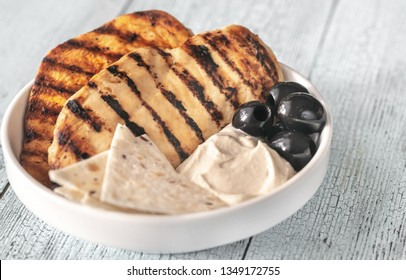 Grilled chicken breast with black olives, tahini sauce and tortilla slices