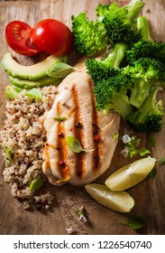 Grilled chicken breast with broccoli and a quinoa on wooden Board. Top view