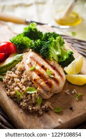 Grilled chicken breast with broccoli and a quinoa on wooden Board. Healthy eating