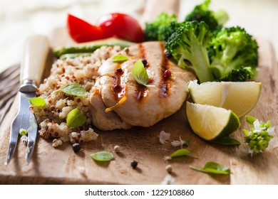Grilled chicken breast with broccoli and a quinoa on a wooden Board. Healthy eating