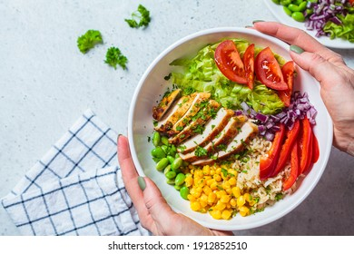 Grilled chicken breast with brown rice and vegetables in a white plate, gray background. Healthy food concept.