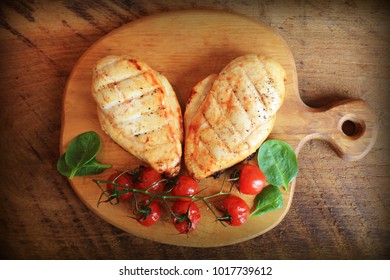 Grilled chicken breast with cherry tomatoes, spinach on a wooden board. Top view