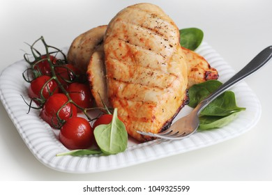 Grilled chicken breast with cherry tomatoes, spinach on a white plate