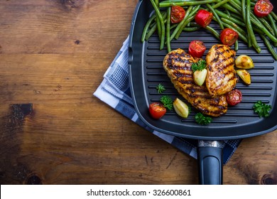 Grilled chicken breast in different variations with cherry tomatoes, green French beans, garlic, herbs, cut lemon on a wooden board or teflon pan.