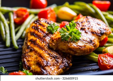 Grilled chicken breast in different variations with cherry tomatoes, green French beans, garlic, herbs, cut lemon on a teflon pan.