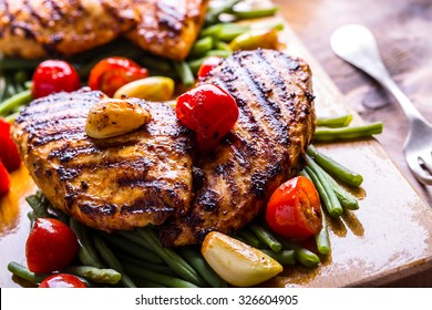 Grilled chicken breast in different variations with cherry tomatoes, green French beans, garlic, herbs, cut lemon on a wooden board.