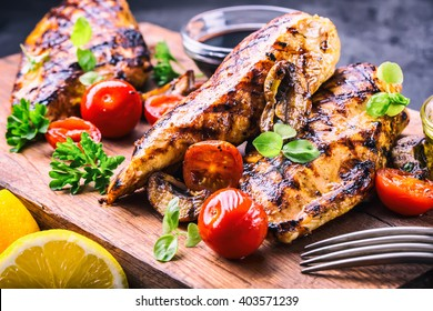 Grilled chicken breast in different variations with cherry tomatoes,  mushrooms, herbs, cut lemon on a wooden board.