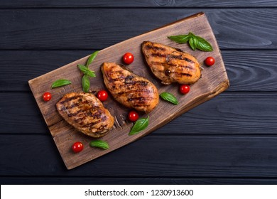 Grilled chicken breast ( fillet ) with basil and tomatoes . BBQ background