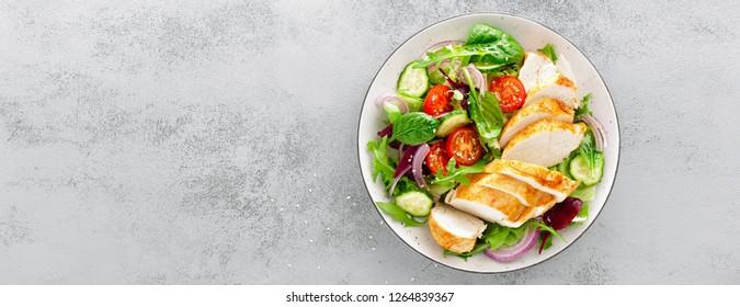Brust, Filet und frischer Gemüsesalat aus Salat, Arugula, Spinat, Gurken und Tomate gegrillt. Gesundes Mittagsmenü. Diät Essen. Draufsicht. Banner