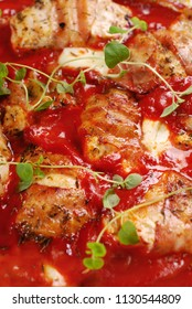 grilled chicken breast fillet with mozzarella and prosciutto stewed in tomato sauce in the pan