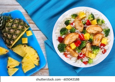 grilled chicken breast fillet with rice, pineapple chunks, stir-fry broccoli and red bell pepper on white plate, half of pineapples with slices on cutting board, view from above