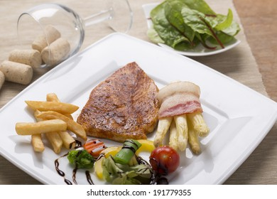 grilled chicken breast with French fries, asparagus, and vegetables