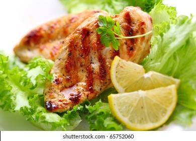 Brust von gegrillten Hühnern mit frischem Salat und Zitrone