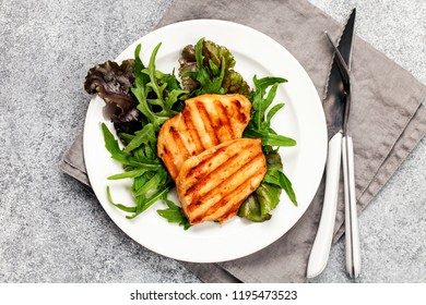 Grilled chicken breast. Fried chicken fillet and fresh vegetable salad of  mangold and arugula leaves. Chicken meat salad. Healthy food. Flat lay. Top view. Gray background