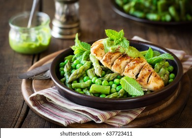 Grilled chicken breast garnished with green peas, asparagus stalks and mint sauce against dark rustic background. Healthy homemade dinner