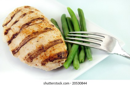 Grilled chicken breast with green beans on a white plate.