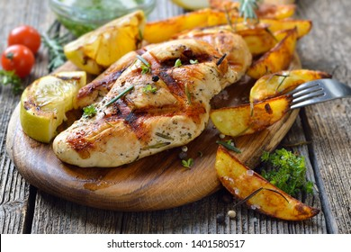 Grilled chicken breast with lemon dipping sauce and rosemary potato wedges