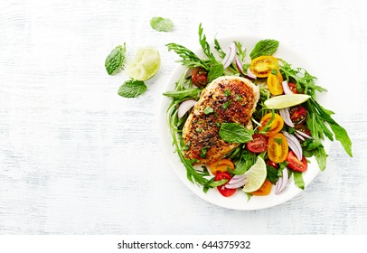 Grilled Chicken Breast on Cherry Tomato and Arugula Salad with Fresh Mint served on white wooden background. Homemade food. Concept for a tasty and healthy meal. Top view. Copy space.