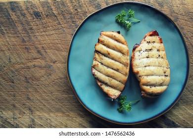 Grilled chicken breast on dark wooden background .