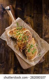 Grilled chicken breast on dark wooden background