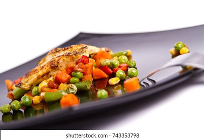 Grilled chicken breast on vegetables bed